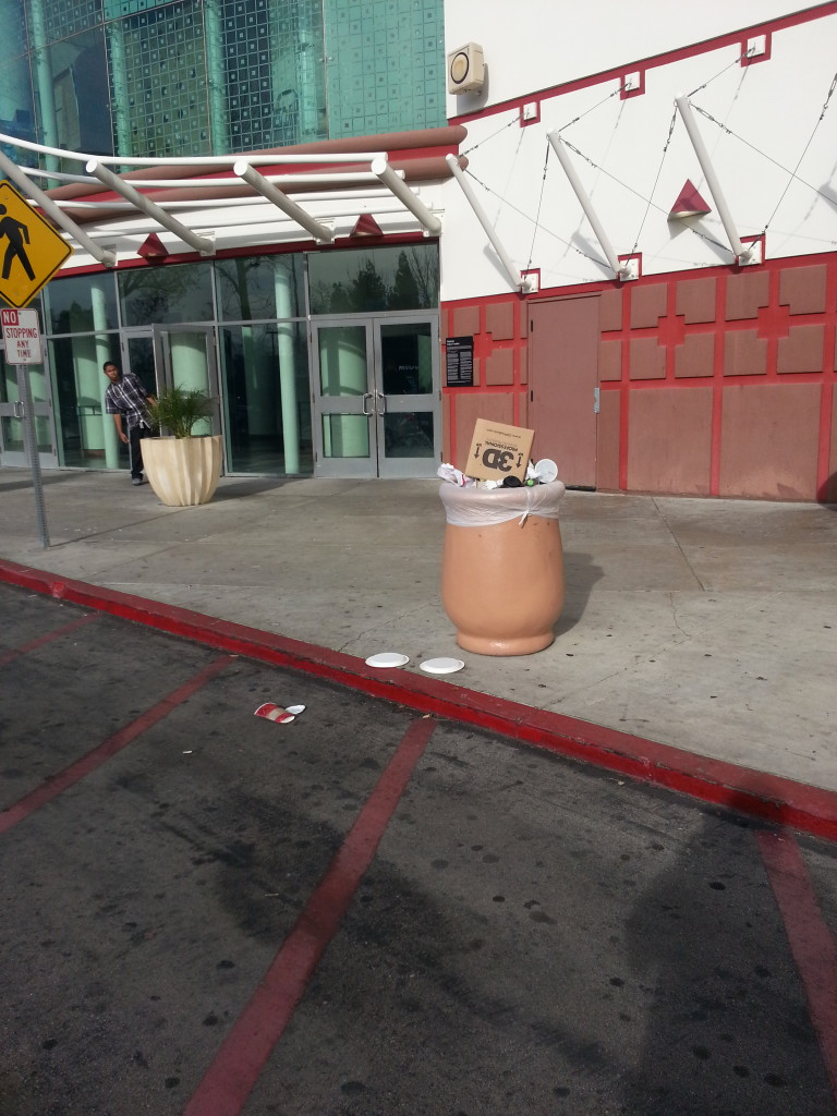 An overflowing trash can outside of the AMC Promenade 16.