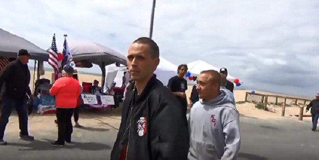 A screenshot showing Hammerskin Nation skinheads at the event. Notice the distinctive crossed hammers on the leading man's jacket.