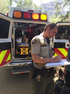 The teenage hiker sits in the ambulance and shown to have injured his right leg.