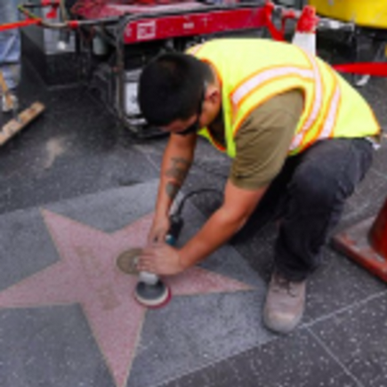 "A worker removes the word ""rapist"" someone had scrawled onto Bill Cosby's Walk of Fame star."