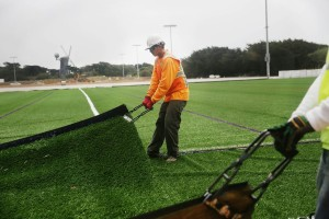 A worker lays a sheet of turf onto the Beach Chalet soccer fields.