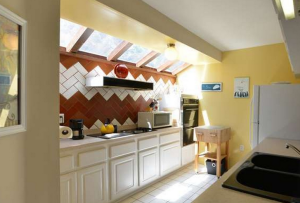 The home's spacious kitchen features a skylight providing it with natural lighting.