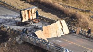 Backwater bridge barricaded by scorched vehicles and debris.
